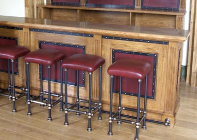AND bespoke blackened steel and antique bronze bar stools