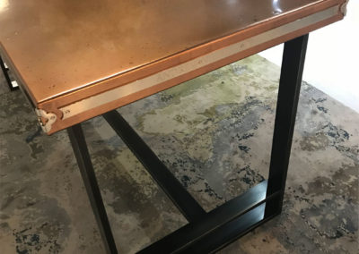 Andrew Nebbett Designs custom made copper top table on Industrial steel frame featured at Christopher Peacock London showroom Design Centre